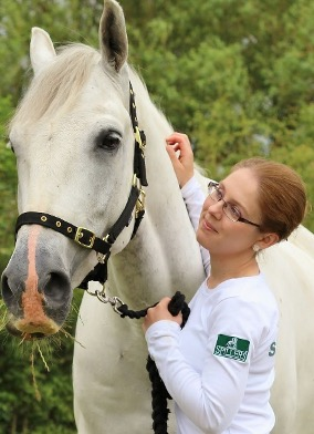 Smiling woman standing next to a white horse